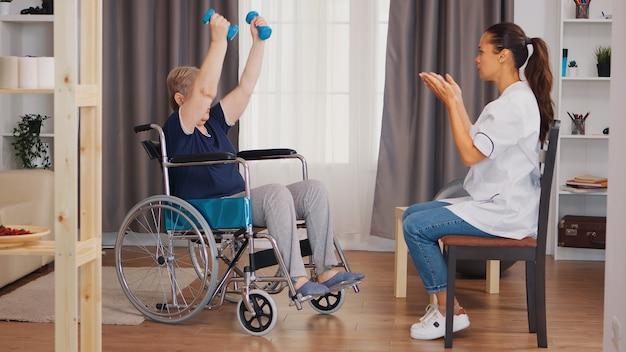 Oude dame in rolstoel oefenen met dumbbels. verpleegkundige helpen met revalidatie. training, sport, herstel en tillen, bejaardentehuis, zorgverpleging, gezondheidsondersteuning, sociale hulp