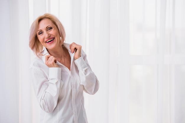 Oude dame met kort haar die gelukkig kijkt