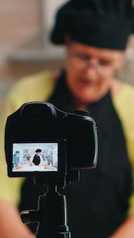 Oude damebakker die voedselrecept presenteert op kookpodcast vanuit de keuken. gepensioneerde blogger-chef-beïnvloeder die internettechnologie gebruikt om te communiceren, bloggen op sociale media met digitale apparatuur