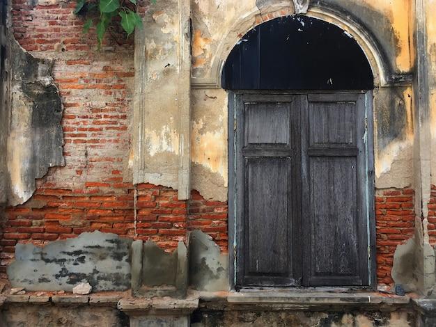 Oude deur en raam van bakstenen gebouw