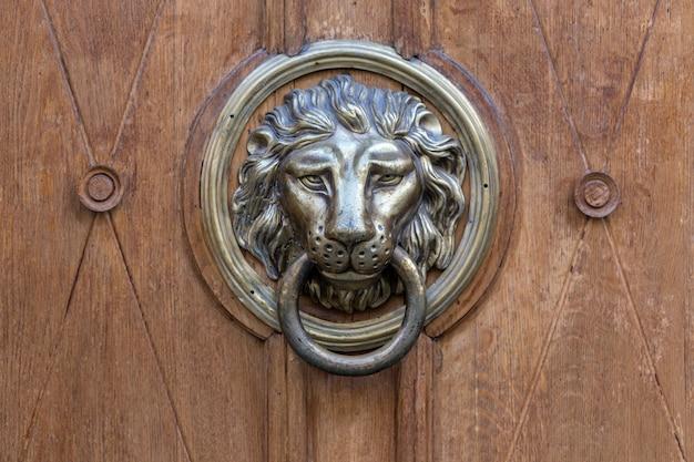 Oude deurklink in de vorm van een metalen leeuw
