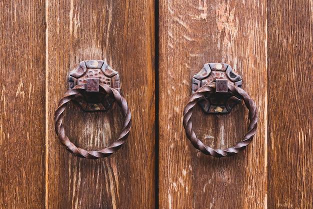 Oude deurknop op een houten deur.