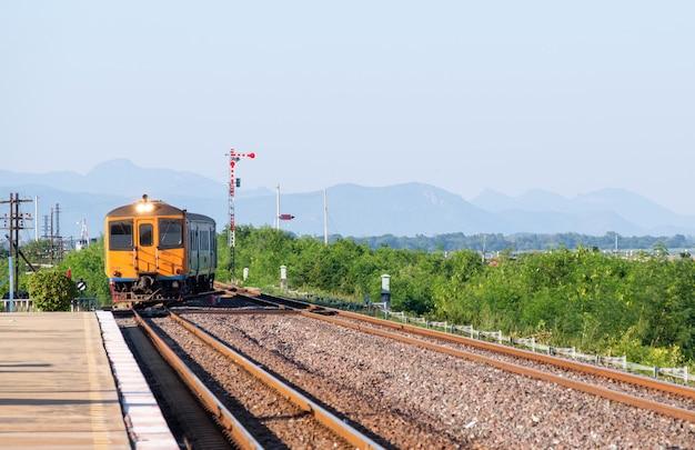 Oude dieselmotor met meerdere eenheden van de lokale trein arriveert op het station in de noordoostelijke lijn, thailand.