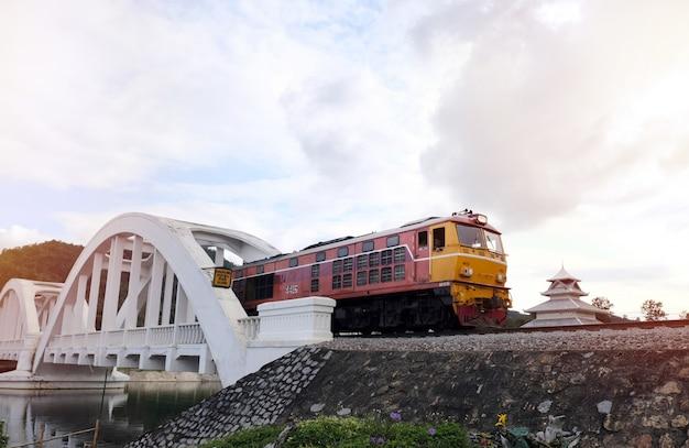 Oude dieseltrein loopt op de brug over de witte brug de beroemde stalen brug in lampoon, thailand