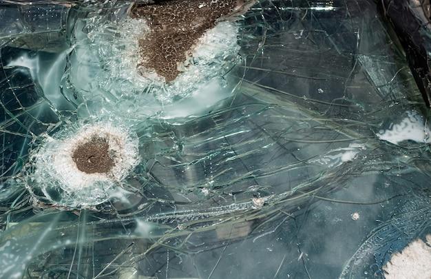 Oude doorstane gebroken kogelvrij glas van auto na het schieten.