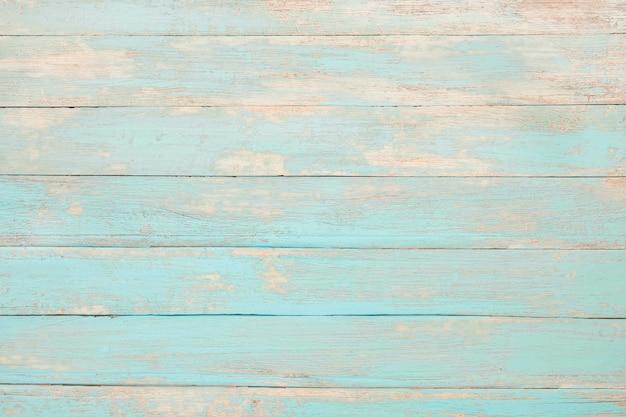Oude doorstane houten plank die in turkooise blauwe pastelkleur wordt geschilderd.
