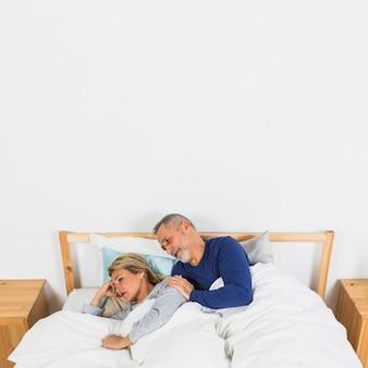 Oude droevige vrouw die dichtbij de mens op bed ligt