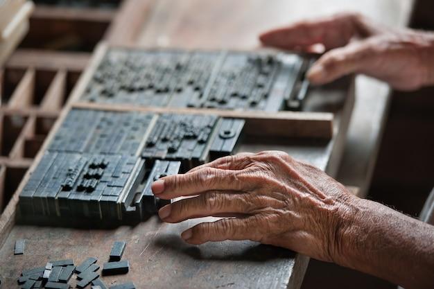 Oude drukwerkindustrie. macrofoto van de man die de letter voor de pers plaatst b
