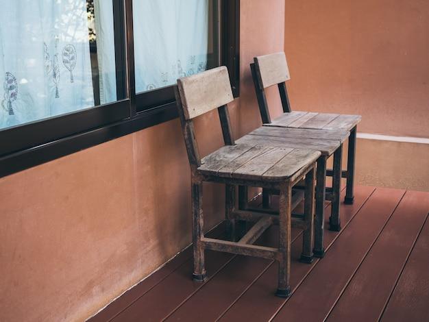 Oude dubbele houten stoel op houten terras voor kamer met glazen raam.