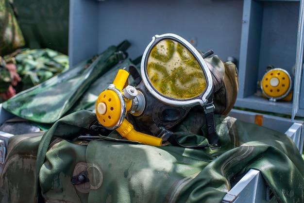 Oude duikuitrusting voor duikers maskervinnen en een groene duikpakkleding om onder water te duiken