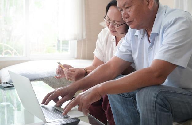 Oude echtparen oefenen met het gebruik van laptops voor online winkelen en betalen.