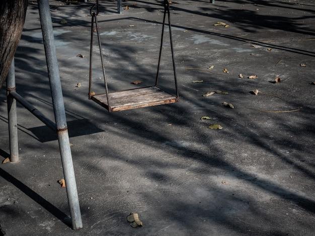 Oude eenzame houten schommeling op zonsondergangtijd met licht en schaduw.