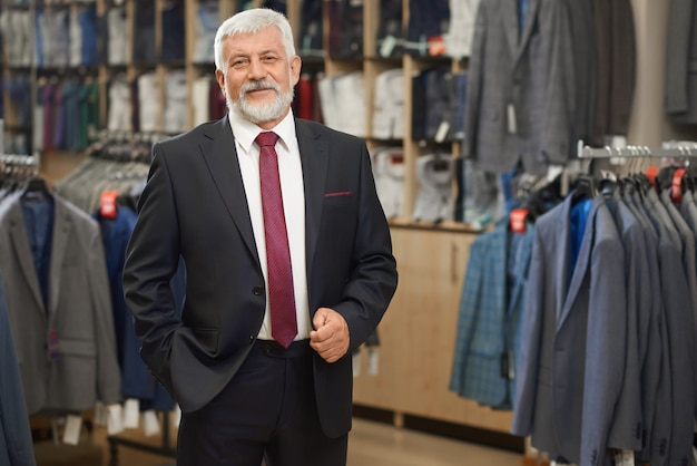 Oude elegante man in grijs kostuum met strikje.
