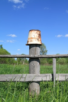 Oude emmer op oude hek