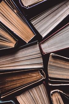 Oude en gebruikte gebonden boeken of tekstboeken van bovenaf gezien. boeken en lezen zijn essentieel voor zelfverbetering, het verwerven van kennis en succes in onze carrières, zakelijke en persoonlijke levens