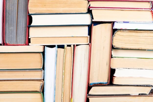 Oude en gebruikte hardback-boeken of tekstboeken van bovenaf gezien. boeken en lezen zijn essentieel voor zelfverbetering, het verwerven van kennis en succes in onze carrière, zakelijke en persoonlijke leven