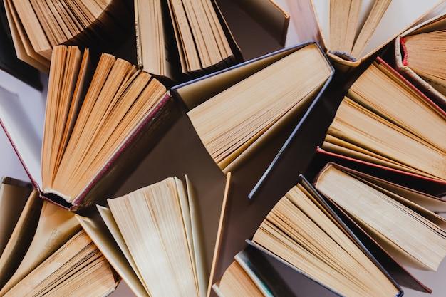 Oude en gebruikte hardcover boeken of schoolboeken zichtbaar van bovenaf. bovenaanzicht van open boeken op tafel.