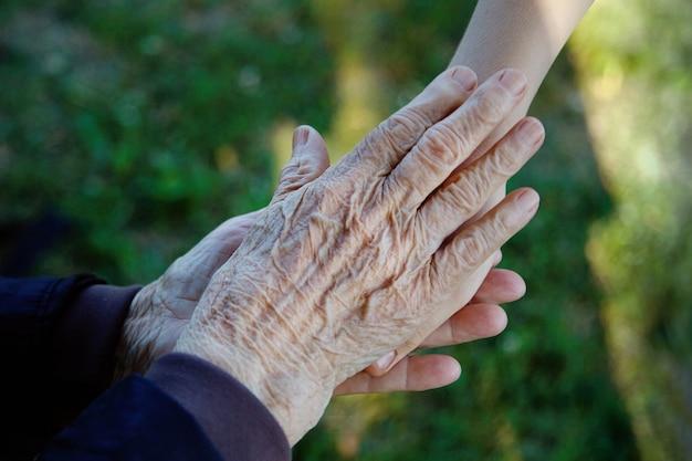 Oude en jonge hand in hand. familie liefde concept.
