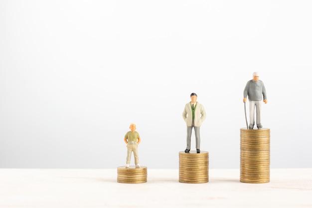 Oude en jonge man staan op stapels gouden munten geïsoleerd op een witte achtergrond