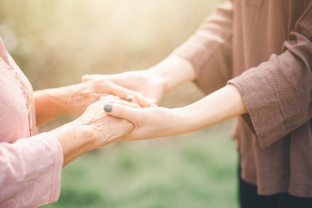 Oude en jonge vrouw hand in hand elkaar zorvuldig in zonlicht