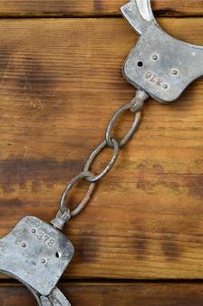 Oude en roestige handcuffs van de politie liggen op een gekraste houten oppervlakte. het concept van een oude misdaad