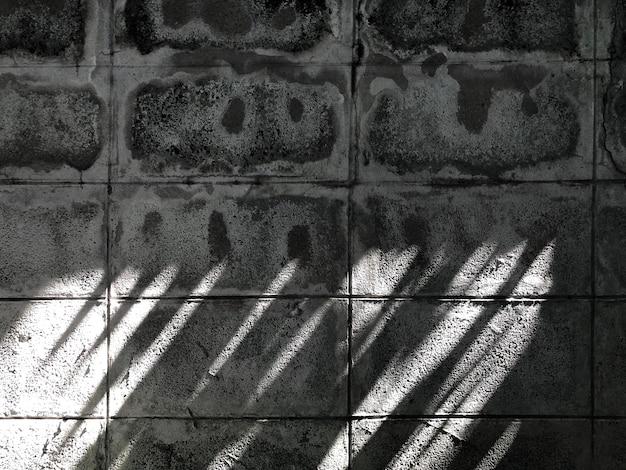 Oude en vuile betonnen omheining met zonlicht en schaduw erop.