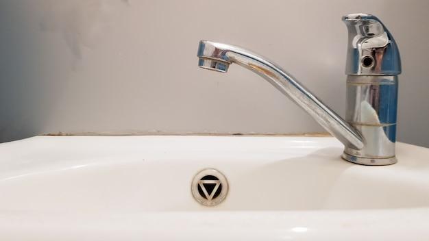 Oude en vuile kraan en witte keramische wastafel, concept van het reinigen, repareren of vervangen van een badkamer, toilet.
