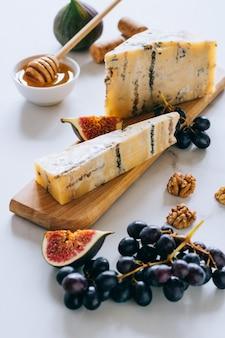 Oude engelse stilton-kaas. blauwe kaas, vijgen en druiven op een marmeren snijplank
