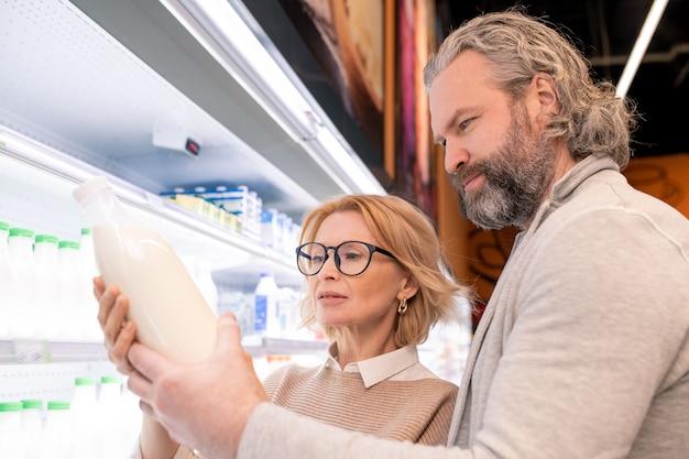 Oude ernstige bebaarde man en zijn blonde vrouw kiezen melk tentoongesteld met zuivelproducten terwijl ze door planken met flessen staan