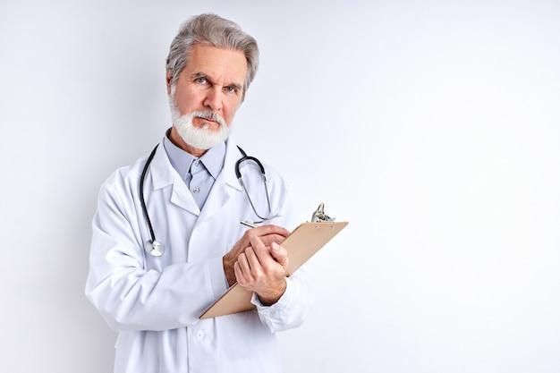 Oude ervaren blanke arts die symptomen oproept en diagnose stelt, tablet gebruikt voor het maken van aantekeningen, medisch uniform draagt, geïsoleerd op witte muurruimte