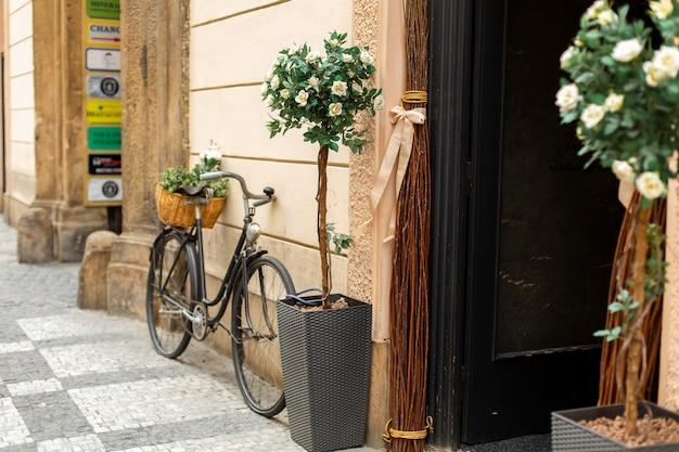 Oude europese stijl, een fiets met een mand met verse bloemen staat geparkeerd bij de ingang van het huis