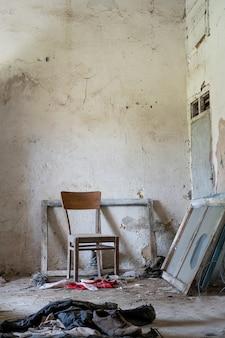 Oude fauteuil midden in een kamer in een verlaten huis