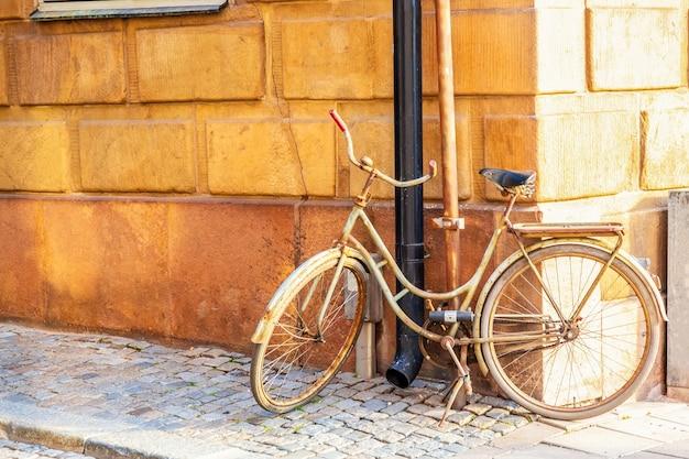 Oude fiets dichtbij geel middeleeuws huis van gamla stan in stockholm