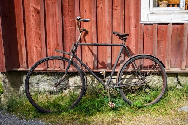 Oude fiets op een houten muur