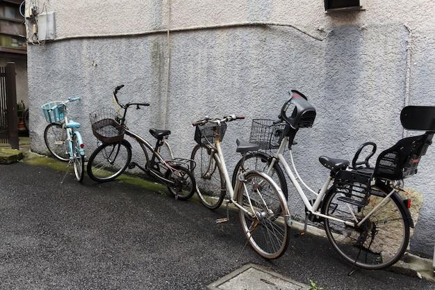 Oude fietsen tegen de buitenmuur van een huis.