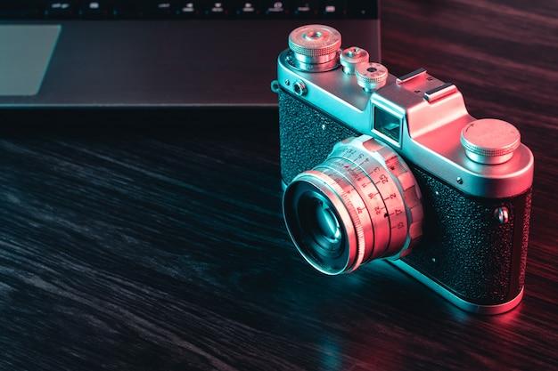 Oude filmcamera en laptop op tafel. blauw en rood licht. uitzicht