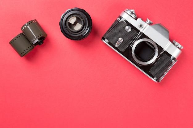 Oude filmcamera met lens en film op rood