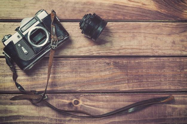 Oude filmcamera met riem en lens op houten achtergrond