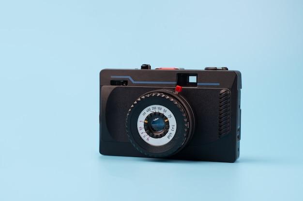 Oude filmcamera op een blauwe achtergrond. creatief retro-ontwerp. trendy vintage accessoires. minimaal plat leggen.
