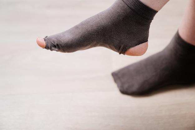Oude gatensok op het been. armoede. gebrek aan geld om nieuwe kleren te kopen.
