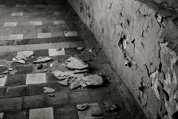 Oude gebarsten grijze muur in een verlaten ziekenhuis