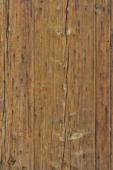 Oude gebarsten langzaam verdwenen houten raadsachtergrond verticaal