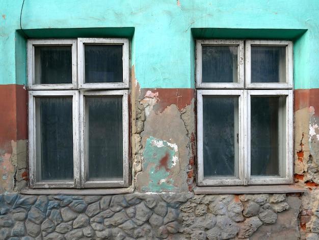 Oude gebarsten muur met een raam