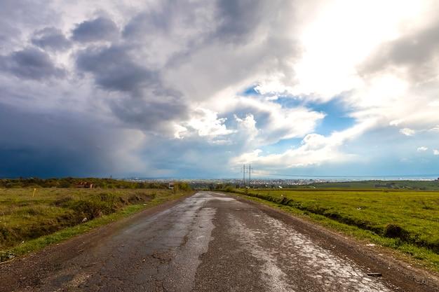 Oude gebarsten weg na regen. slechte hobbelige straat met gaten en stormachtige bewolkte hemel.