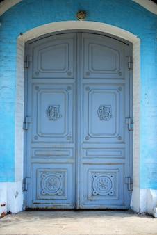 Oude gebogen blauwe deur naar de kerk
