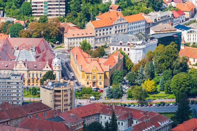 Oude gebouwen en rijdende auto's op de straatmening van bovenaf in brasov