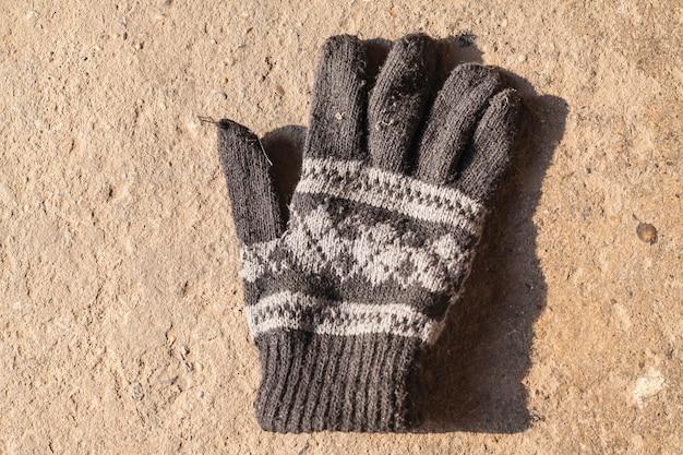 Oude gebreide handschoenen met patroon op betonnen vloer
