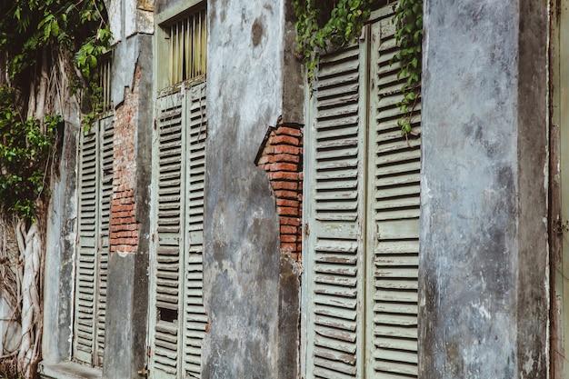 Oude gebroken muren met oude houten ramen van verlaten huis