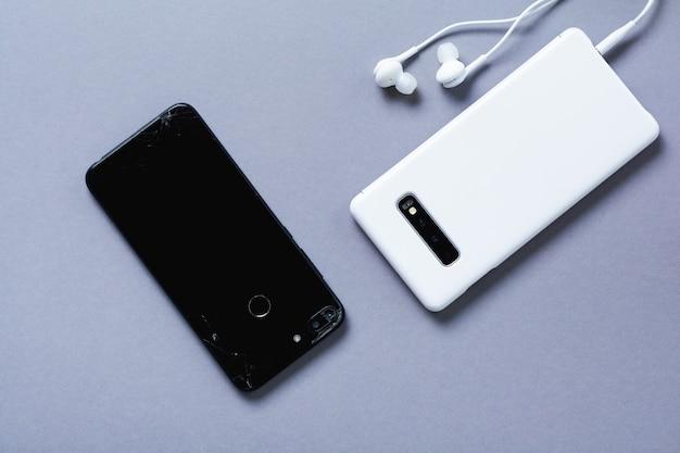 Oude gebroken zwarte en nieuwe witte smartphones op grijze achtergrond. het concept van het recyclen van telefoons en technologieën. bovenaanzicht.