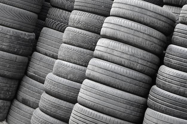 Oude gebruikte banden die met hoge stapels in de garage van de secundaire autodelenwinkel worden gestapeld